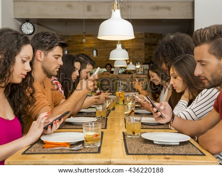 Group of friends at a restaurant with all people on the table occupied with cellphones - stock photo