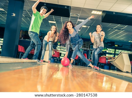 Group of friends at bowling - Young people having fun at bowling,one girl is throwing ball and friends supports her - stock photo