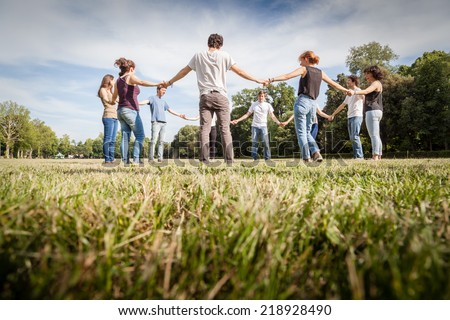 Group of friends at park holding hands. View from below - stock photo
