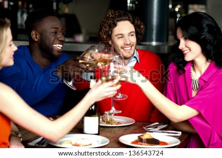 Group of friends at the bar raising their glasses for a toast.