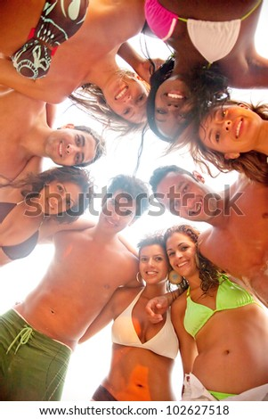 Group of friends at the beach smiling and hugging - stock photo