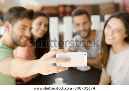 Group of friends at the coffee shop making a selfie together