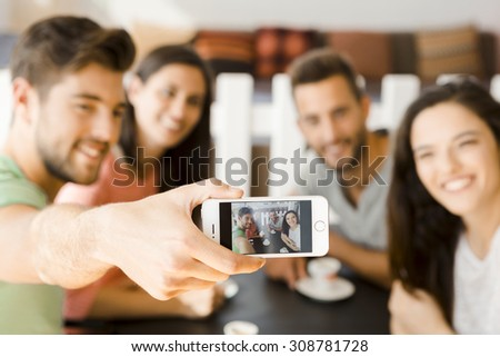 Group of friends at the coffee shop making a selfie together  - stock photo