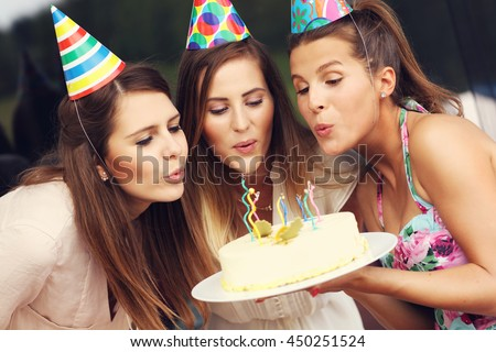 Group of friends blowing candles on birthday cake - stock photo