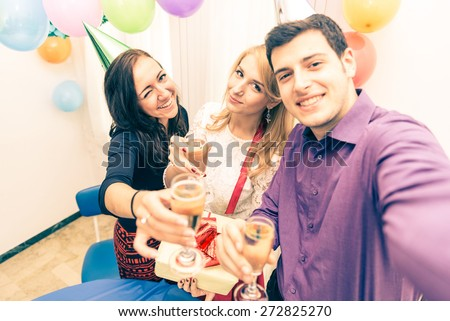 Group of friends celebrating birthday - Young man holding camera and taking a picture with camera while at his girlfriend's party - Attractive people at party toasting champagne glasses and having fun - stock photo