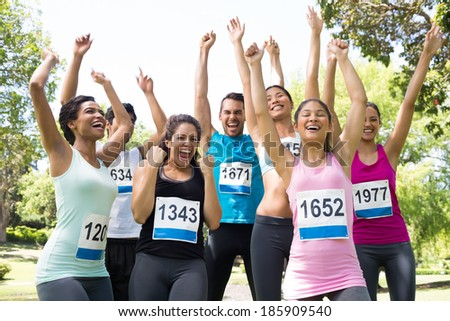 Group of friends cheering after winning a race in the park - stock photo