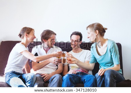group of friends cheering at home, happy young smiling people with drinks, copyspace