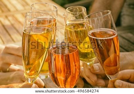 Group of friends clinking glasses of champagne with orange colors outdoors