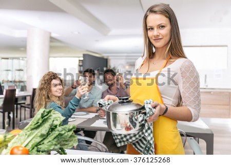 Group of friends cooking at home to have dinner together. spending time with old friends and sharing good mood - stock photo