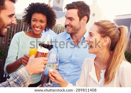 Group of friends drinking at a rooftop bar - stock photo