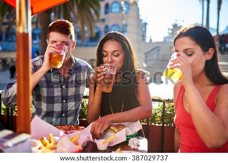 group of friends drinking beer together at outdoor bar and grill in summer sun