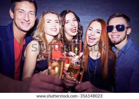 Group of friends drinking champagne and celebrating holiday