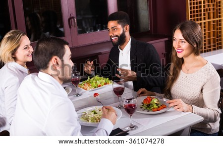 Group of friends eating at restaurant table and chatting