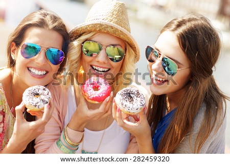 Group of friends eating donuts in the city - stock photo