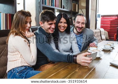 Group of friends ein cafe looking at smartphone - stock photo