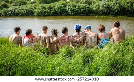 group of  friends embracing sitting in a row rear view - stock photo