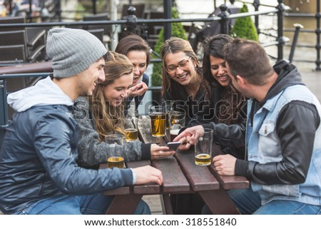 Group of friends enjoying a beer at pub in London and looking at a smart phone,  laughing and looking each other. They are four girls and two boys in their twenties. - stock photo