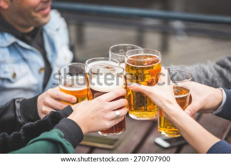 Group of friends enjoying a beer at pub in London, toasting and laughing. They are four girls and two boys in their twenties. Close up and focus on glasses. - stock photo