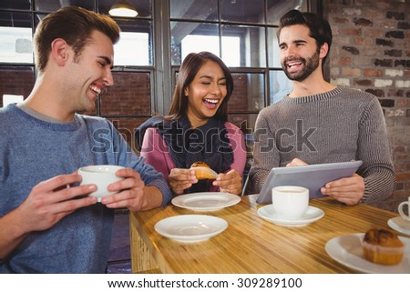 Group of friends enjoying a dessert with tablet in a cafe - stock photo