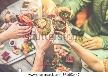 Group of friends enjoying appetizer in american bar - Young people hands cheering with wine and tropical fruits cocktails - Radial purple and green filters editing - Focus on left hands glasses
