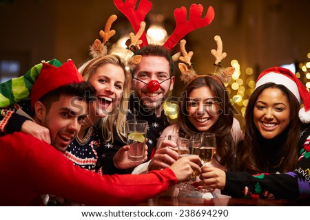 Group Of Friends Enjoying Christmas Drinks In Bar - stock photo