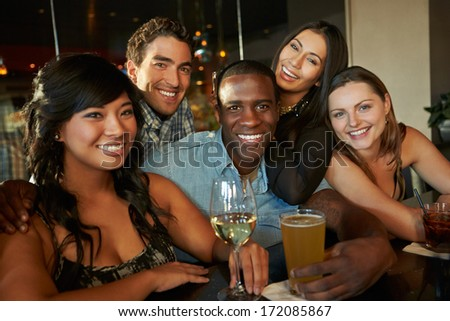 Group Of Friends Enjoying Drink At Bar Together