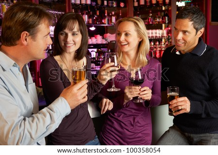 Group Of Friends Enjoying Drink Together In Bar - stock photo