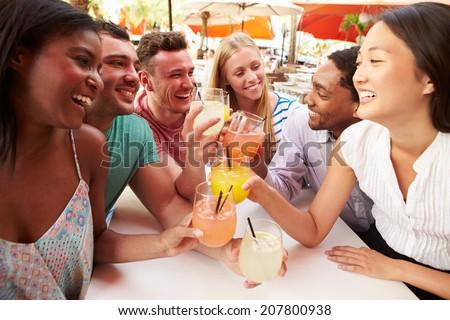 Group Of Friends Enjoying Drinks In Outdoor Restaurant - stock photo