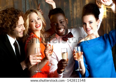 Group of friends enjoying drinks in restaurant bar - stock photo