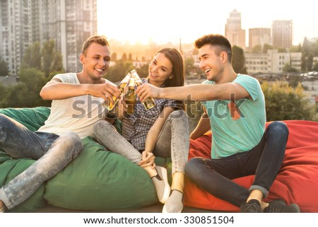 Group of friends enjoying drinks outdoors at roof while having party. They cheerfully smiling and sitting on bag chairs. Nice city panorama - stock photo