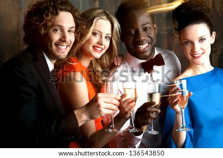 Group of friends enjoying drinks together in restaurant bar. - stock photo