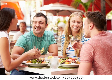 Group Of Friends Enjoying Lunch In Outdoor Restaurant - stock photo