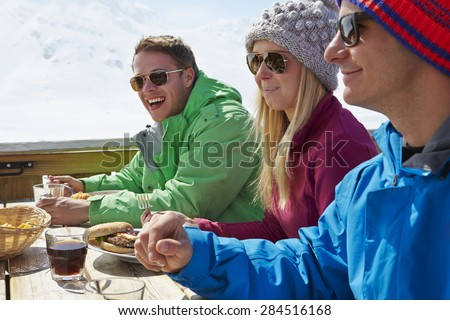 Group Of Friends Enjoying Meal In Cafe At Ski Resort - stock photo