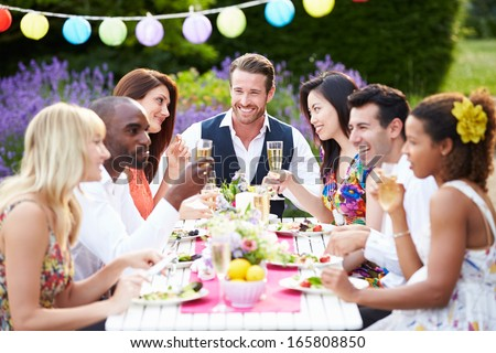 Group Of Friends Enjoying Outdoor Dinner Party - stock photo