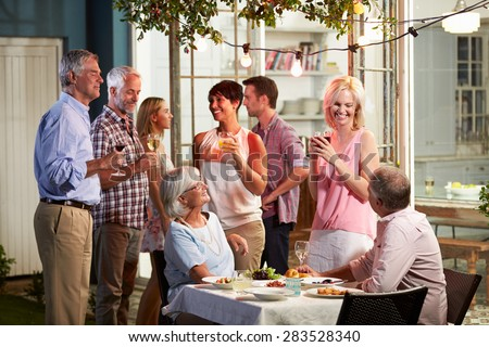 Group Of Friends Enjoying Outdoor Evening Drinks Party - stock photo