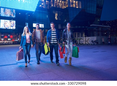 Group Of Friends Enjoying Shopping Trip Together group of happy young frineds enjoying shopping night and walking on steet on night in with mall in background - stock photo
