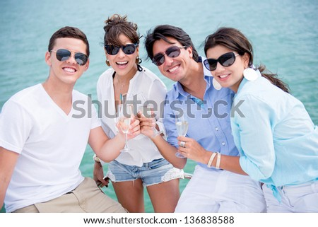 Group of friends enjoying the summer drinking champagne and sailing - stock photo