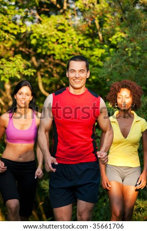 Group of friends exercising - man and two women jogging outdoors in beautiful evening light - stock photo
