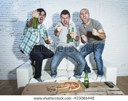 group of friends fanatic football fans watching soccer game on television celebrating goal jumping on couch screaming excited and ecstatic and crazy happy with beer bottles and pizza - stock photo