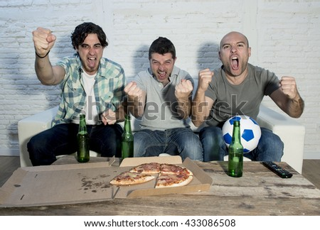 group of friends fanatic football fans watching soccer game on television celebrating goal on couch screaming excited and ecstatic in crazy happy face expression with beer and pizza - stock photo