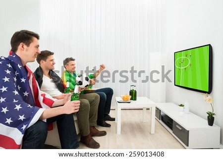 Group Of Friends From Different Nations Holding Beer Bottle Watching Football On Television - stock photo