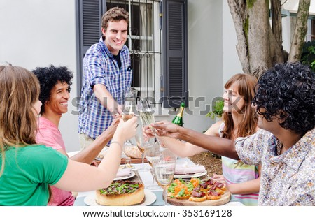 Group of friends gathered and sharing a toast of champagne, celebrating a special occasion in a casual garden outdoor setting with delicious platters of food on the table