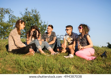 Group of friends hanging out, sitting on grass at the park. Having a drink on sunny day