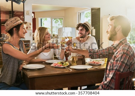 Group of friends  having a nice aperitif on a rustic wooden table in a lovely house. They are having fun and talking in front of glasses of white wine and tomatoes mozzarella - real people