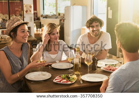 Group of friends having a nice aperitif on a rustic wooden table in a lovely house. They are having fun and talking in front of glasses of white wine and tomatoes mozzarella - real people - stock photo