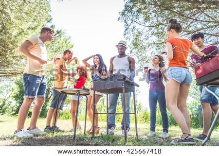 Group of friends having fun at barbecue party outdoors - People grilling, dancing and drinking wine