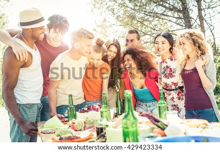 Group of friends having fun at the house barbecue. Eating and sharing good moods - stock photo