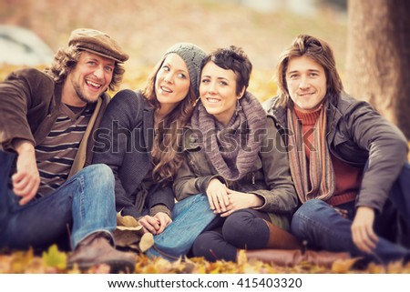 group of Friends having fun at the park  in autumn