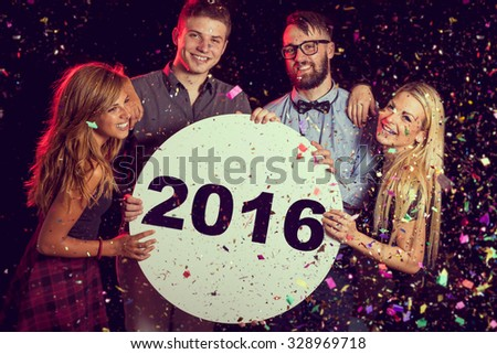Group of friends having fun, celebrating New Year's Eve and holding cardboard circle with 2016 written on it - stock photo