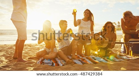 Group of friends having fun enjoying a beverage and relaxing on the beach at sunset
